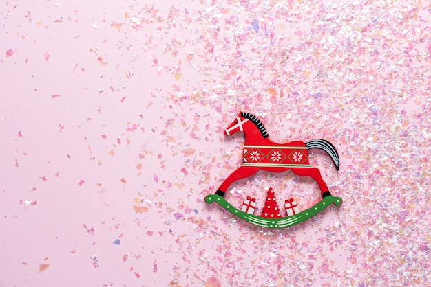 Brinquedo de natal do cavalo de balanço em rosa com glitter. configuração plana