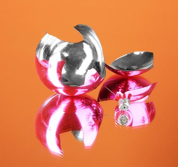 Brinquedo de natal quebrado em fundo laranja