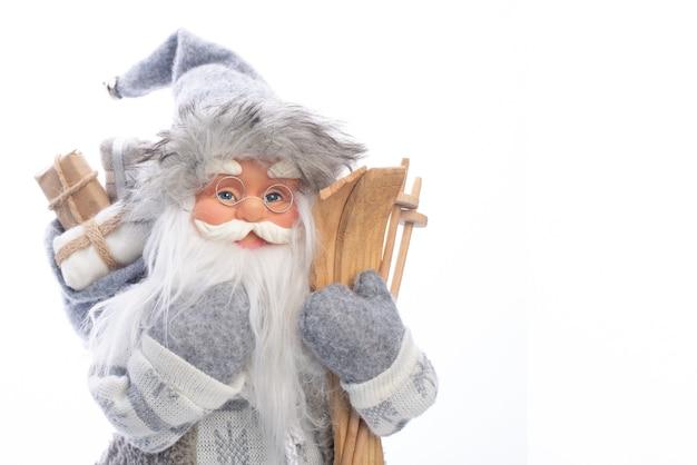 Brinquedo de papai noel com presentes em uma mão e equipamentos de esqui na outra mão isolado no branco.