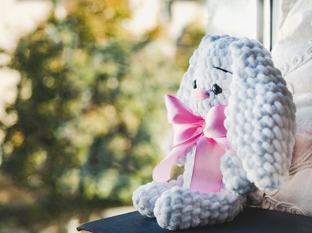 Brinquedo de pelúcia brilhante, sentado em um peitoril da janela