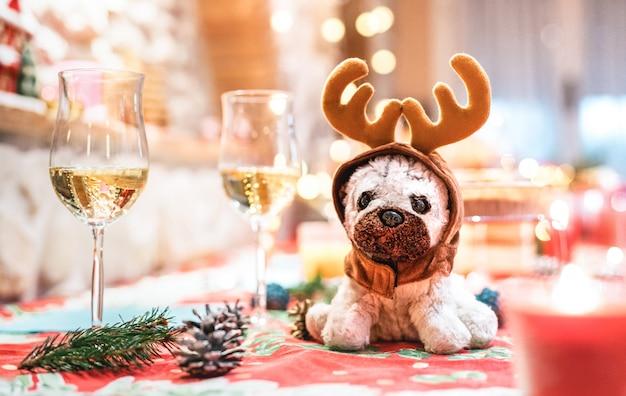 Brinquedo de pelúcia cachorro usando orelhas de rena, sentado em cima da mesa perto de taças de champanhe no fundo de férias de natal
