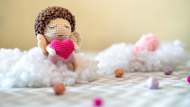Brinquedo de pelúcia fofo de malha no sofá com pelúcia em volta