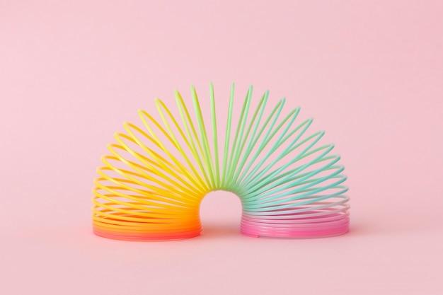 Brinquedo de plástico arco-íris em fundo rosa