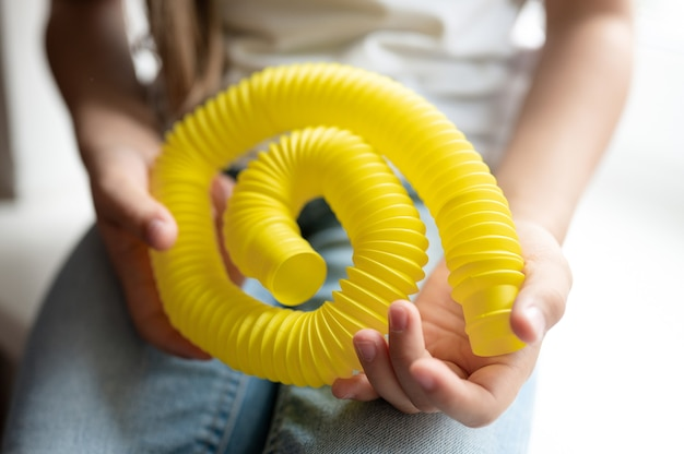 Brinquedo de plástico com tubo sensorial anti-stress nas mãos de uma criança. uma menina criança feliz brinca com um brinquedo de agitação poptube em casa. crianças segurando e brincando de tubo pop de cor amarela, tendência 2021 ano