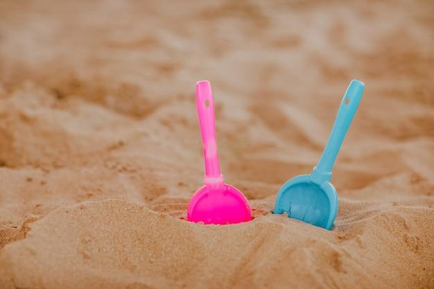 Brinquedo de plástico rosa e azul na costa do mar de areia