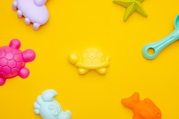 Brinquedo de praia de plástico cor pastel em fundo amarelo. o desenvolvimento do conceito de motor fino. jogo de criatividade e vista superior do conceito de verão
