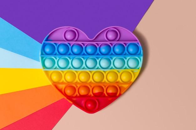 Brinquedo de silicone com coração de arco-íris em um fundo colorido nas cores