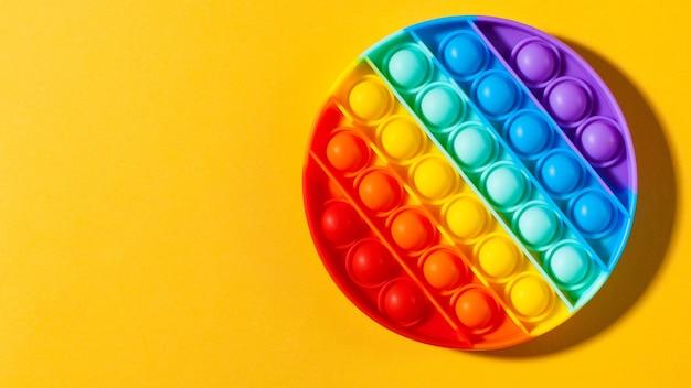 Brinquedo de silicone pop it sobre fundo amarelo, brinquedo antiestresse, uma tendência no espaço de cópia de brinquedos para crianças