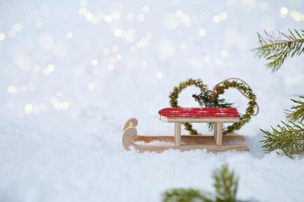 Brinquedo de trenó de fundo de natal, coração feito de abeto na neve com bokeh copyspace