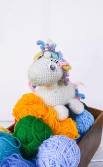 Brinquedo de unicórnio de crochê feito à mão e fios de colorul em uma caixa de madeira com fundo branco.