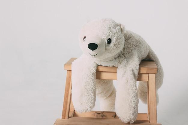 Brinquedo de urso polar branco velho engraçado na cadeira de madeira
