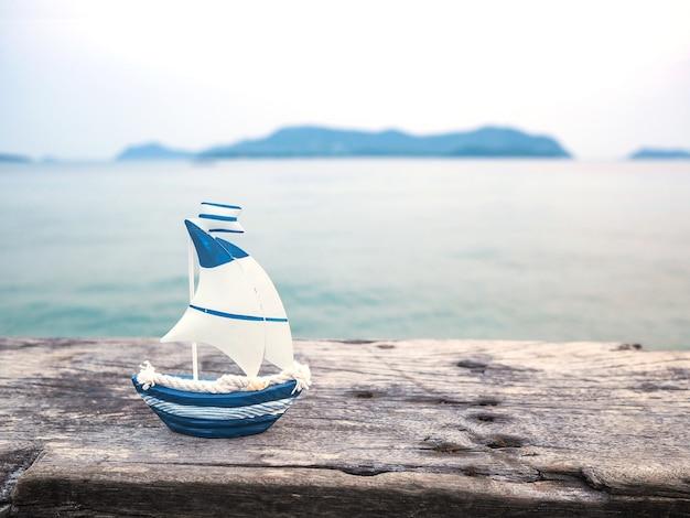 Brinquedo do bote na prancha de madeira sobre o fundo do mar.