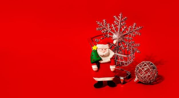 Brinquedo do carrinho de compras com brinquedos de natal e parede vermelha. copie o espaço. descontos, venda. liquidação de natal e ano novo.