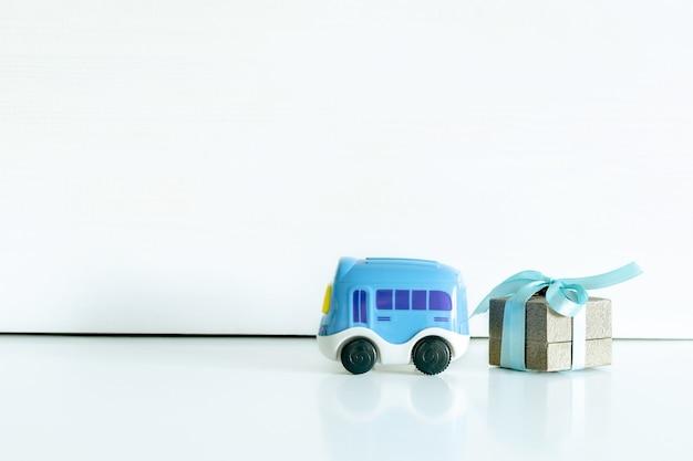 Brinquedo do carro azul, caixa de presente na mesa branca com espaço de cópia. chá de bebê, acessórios, coisas, presentes para feliz aniversário de menino menina.