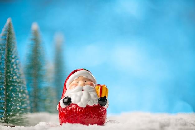 Brinquedo do papai noel e árvores de natal em fundo azul