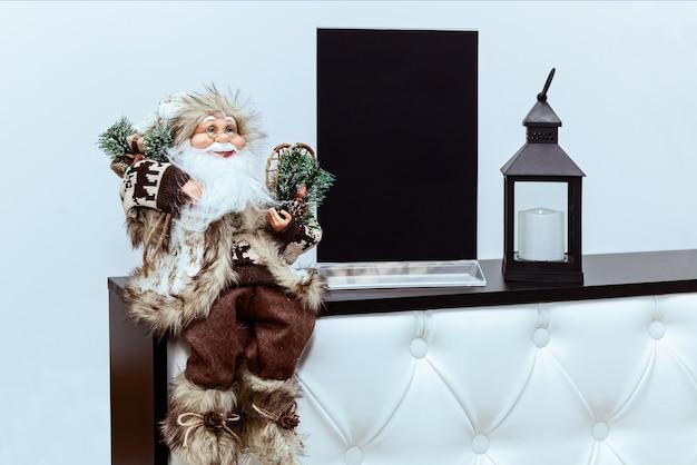 Brinquedo do papai noel e uma lanterna com uma vela na recepção do escritório. decorações de escritório de ano novo.