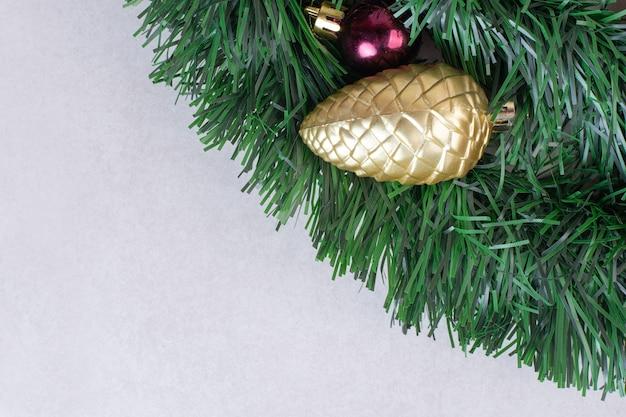 Brinquedo dourado de pinha em enfeites verdes na superfície branca