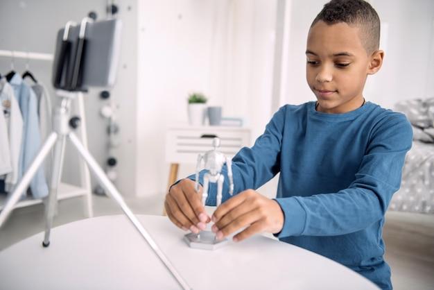 Brinquedo em ação. agradável blogueiro afro-americano gravando vídeo enquanto testa o brinquedo