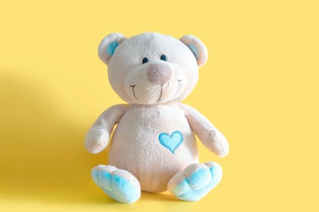 Brinquedo fofo e fofo urso de pelúcia marrom sentado na parede amarela com espaço de cópia