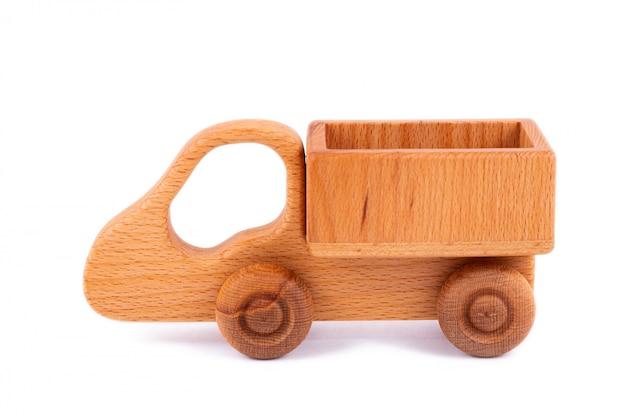 Brinquedo infantil close-up de madeira natural sob a forma de um caminhão basculante em branco