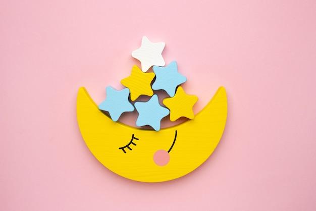 Brinquedo infantil para o desenvolvimento de habilidades motoras, lua crescente com balanceador de estrelas, vista superior de fundo rosa Foto Premium