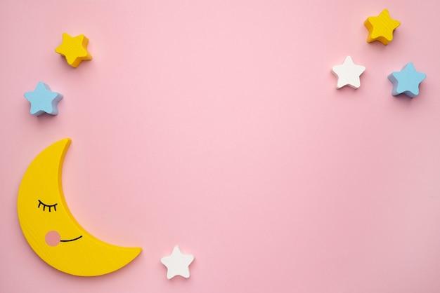 Brinquedo infantil para o desenvolvimento de habilidades motoras, lua crescente com balanceador de estrelas, vista superior de fundo rosa