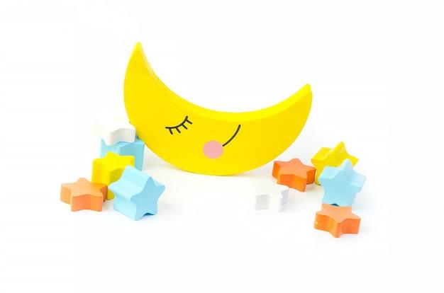 Brinquedo infantil para o desenvolvimento de habilidades motoras, uma lua crescente com estrelas, sobre um fundo branco.