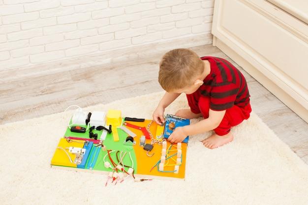 Brinquedo infantil sensorial feito à mão, o menino de três anos brinca com a prancha