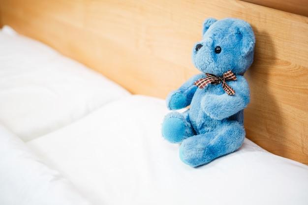 Brinquedo macio na cama, ursinho de pelúcia em uma cama infantil vazia e limpa. cama sem filho