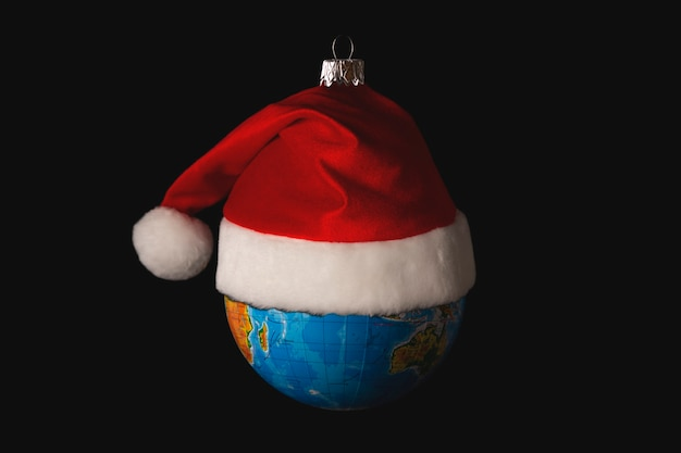 Brinquedo para árvore de natal na forma de um globo ou planeta terra com um chapéu de papai noel conceito de proteção ambiental