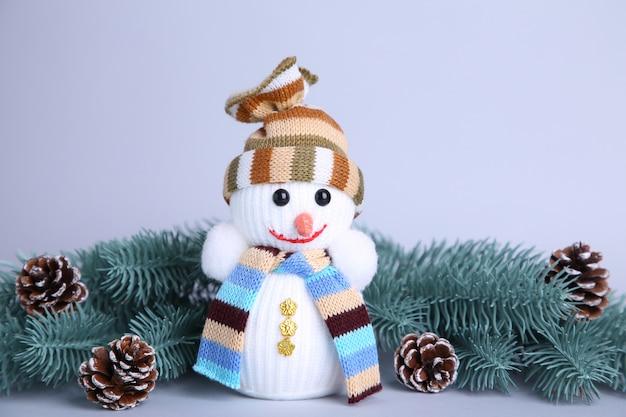 Brinquedo pequeno boneco de neve em um galho de abeto de fundo cinza wuth
