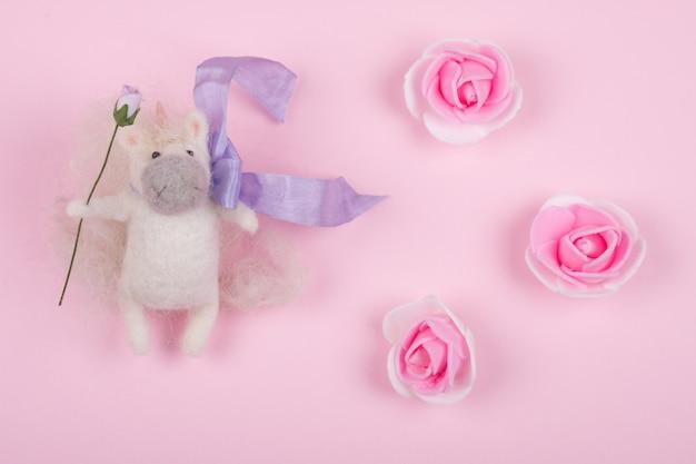 Brinquedo pequeno unicórnio feito de lã e botões de rosa artesanais