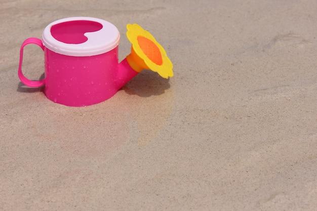 Brinquedo regador na areia da costa do mar.