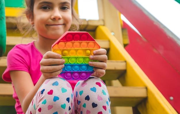 Brinquedo sensorial antistress colorido fidget push pop-lo nas mãos da criança. foco seletivo. natureza.