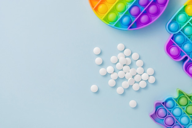 Brinquedo sensorial poppit e pílulas em fundo azul como medicamento para tdah ou autismo