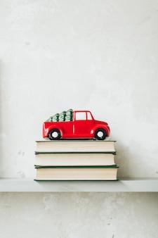 Brinquedo tradicional de carro vermelho de natal com pinheiro no telhado em pé sobre livros