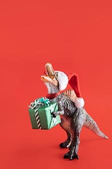 Brinquedo tyrannosaurus rex segurando uma caixa de presente