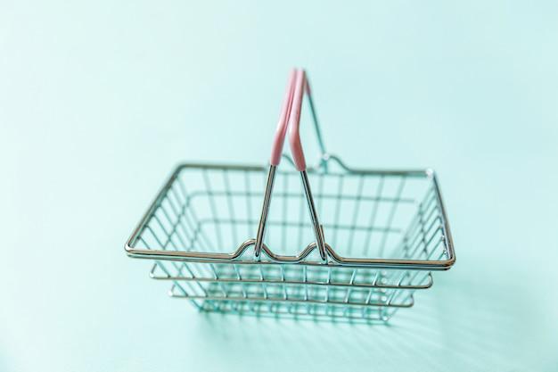 Brinquedo vazio pequeno da cesta de compras na mercearia do supermercado isolado na parede na moda colorida pastel azul. copie o espaço. venda comprar shopping mercado loja compras on-line conceito consumidor.