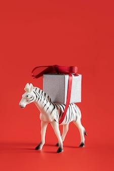 Brinquedo zebra carregando caixa de presente