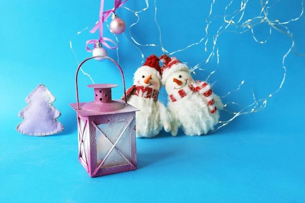 Brinquedos bonecos de neve com chapéus de papai noel, uma lanterna com uma vela acesa e decorações em um fundo azul brilhante