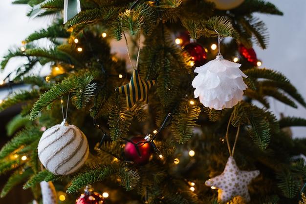 Brinquedos bonitos da árvore de natal na árvore de natal com luzes
