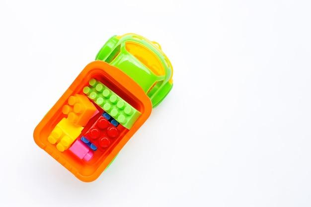 Brinquedos coloridos para crianças na parede branca.