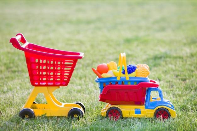 Brinquedos coloridos plásticos brilhantes para crianças ao ar livre num dia ensolarado de verão. carro caminhão carregando cesta com brinquedo frutas e legumes e carrinho de compras.