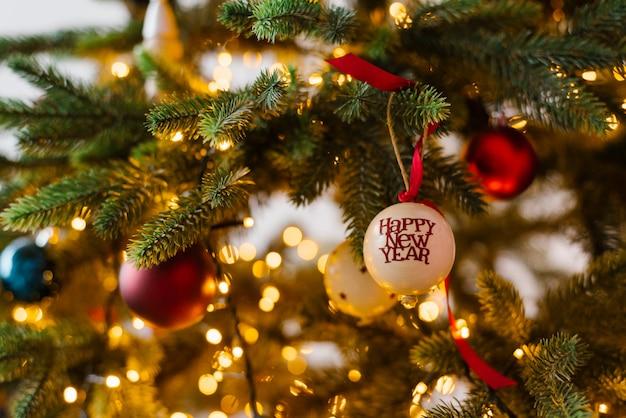 Brinquedos da árvore de natal na árvore de natal com luzes