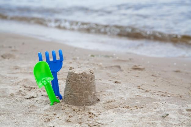 Brinquedos de areia na praia perto da água