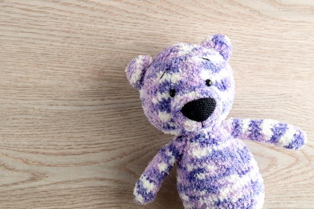 Brinquedos de artesanato para crianças. urso de pelúcia artesanal. mesa de madeira vista superior mock up