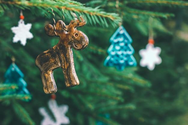 Brinquedos de cerâmica incomuns na forma de um alce, uma árvore de natal e flocos de neve pendurados em um galho de abeto. decorações para o ano novo, clima festivo