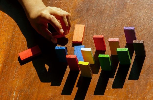 Brinquedos de madeira coloridos, brinquedos educativos de lógica para crianças com mão de criança de perto, ao sol da manhã
