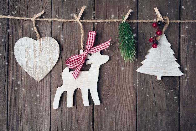 Brinquedos de madeira de natal em uma corda sobre fundo de madeira cartão de ano novo