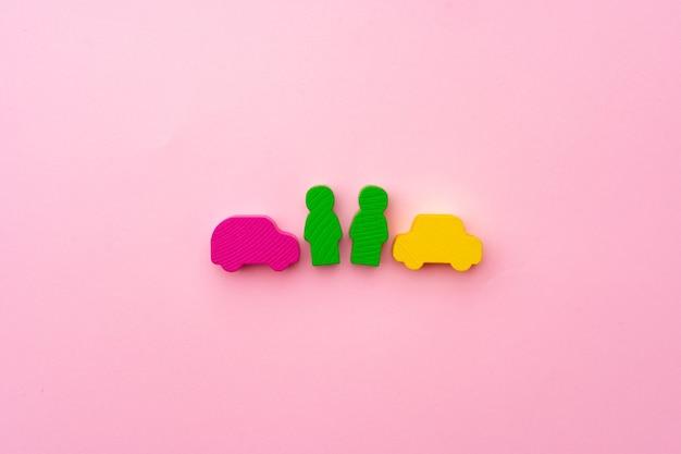 Brinquedos de madeira de pessoas e carros na superfície rosa
